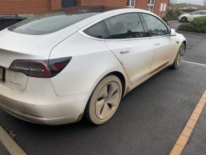 A very dirty white Tesla Model 3